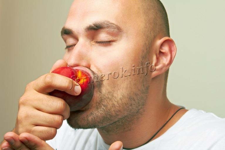 Мужчина кушает персик